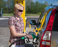Young Woman Refilling Car Tank in Gas Station