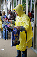 Italy. Province of Veneto. Castelnuovo del Garda. A tourist, wearing a yellow plastic rain coat, is looking at the map of the park. He holds in his hand a plastic bag celebrating the 30th birthday of the park ( 1975 - 2005).  Gardaland is the biggest amusement park in Italy and one of the largest in the whole of Europe. © 2006 Didier Ruef