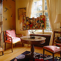 In the bedroom a 3D painted panel by Jean Tinguely is displayed on a pedestal table standing on a rug with a pattern designed by Roger Nellens
