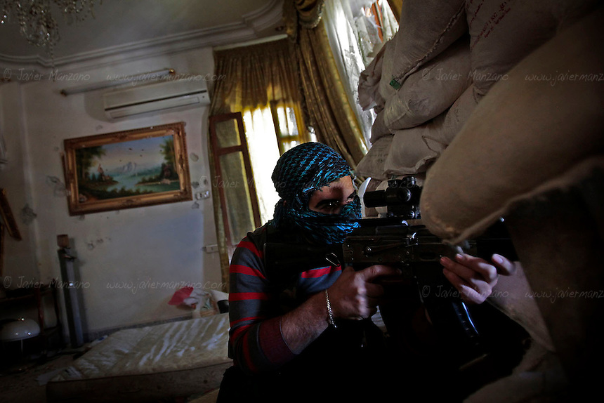 A Free Syria Army sniper mans his position near the Garage Al-Hajez crossing in the Bustan Al-Qasr neighborhood of rebel-controlled Aleppo. At this site thousands of civilians who live in the Free Syria Army side of the city travel to the regime areas to work everyday (or to seek employment). During their daily commute, men, women and children walk over a makeshift bridge that was constructed over the canal in order to work, shop or sell goods in the government-controlled areas of the city where life still maintain a semblance of normality (despite daily shelling by members of the Free Syria Army). Dozens are shot each day by snipers holed up on the high ground of the buildings overlooking the rebel zones. Victims claim that they were shot by bullets that originated in areas under regime control.