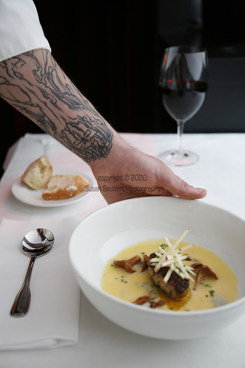 Waiter placing a bowl of soup on the table