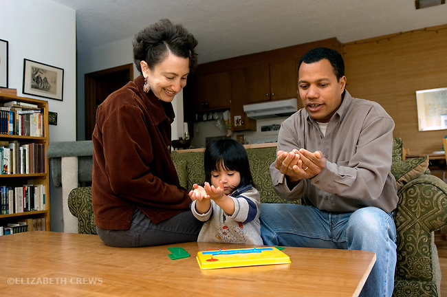 """Berkeley CA Adoptive parents and Guatemalan daughter, two-years-old, using signing to name """"boat"""" in puzzle she's doing  MR"""