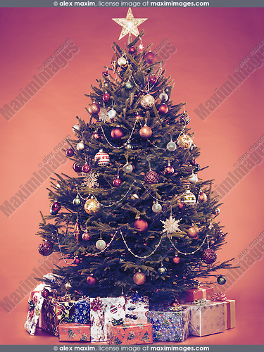 Beautiful decorated vintage stylized Christmas tree with wrapped gifts under it. Isolated on brown background.