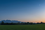 Crescent moon rising over hayfield and Olympic Mountains, Agnew WA near Port Angeles