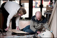 BNPS.co.uk (01202 558833).Pic: RachelAdams/BNPS..Dave's wife Margaret helps him start to pick up the pieces...A jigsaw creator who spent over a month making a 40,000 piece puzzle for a world record attempt has had to start again - as it collapsed just one day after he finished...Craftsman Dave Evans from Weymouth in Dorset was hoping to create the largest hand-cut wooden jigsaw and spent 35 days making it out of 33 images of the Queen's Diamond Jubilee...Just one day after he put in the final segment of the 19ft 6in by 8ft masterpiece, Dave noticed it had moved slightly due to the sloping floor, and tried to adjust it...But as he moved the enormous puzzle he became distracted by someone asking for directions, and it suddenly collapsed from the frame and crumpled to the floor...Luckily Dave had already measured, photographed, and filmed the world record bid and sent the information off to the Guiness World Records before it was destroyed..