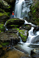 A man stands next to a roaring waterfall and mountain stream in North Carolina.