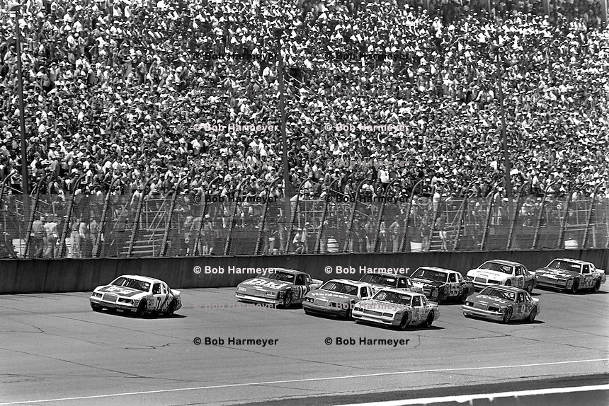 BROOKLYN, MI - AUGUST 11: Kyle Petty, driving the Wood Brothers Ford, leads a group of cars on the front straight during the Champion Spark Plug 400 NASCAR Winston Cup race at the Michigan International Speedway near Brooklyn, Michigan, on August 11, 1985.