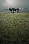B-25 Mitchell bomber aeroplane and crew at dawn on grass runway