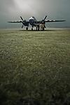 B-25 Mitchell bomber aeroplane and crew at dawn on grass runway
