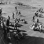 Crew members swing into action immediately following an attack on a U.S. aircraft carrier (unnamed)  during operations off Luzon Island, Philippines. (Although the cption does not state it, this might be a drill and not actual action.)