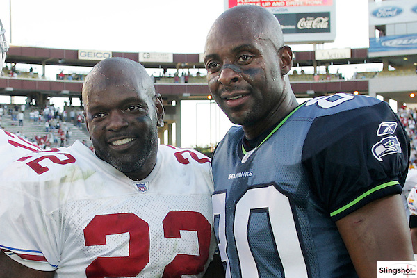 Two legends of the game, Emmitt Smith and Jerry Rice meet at midfield after the game to share a few words and a few smiles....