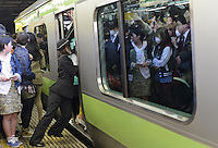 A Railway staff squeezes passengers into full trains during morning rush hour, Shinjuku Station, Tokyo. With up to 4 million passengers passing through it every day, Shinjuku station, Tokyo, Japan, is the busiest train station in the world. The station was used by an average of 3.64 million people per day.  That&rsquo;s 1.3 billion a year.  Or a fifth of humanity. Shinjuku has 36 platforms, and connects 12 different subway and railway lines.  Morning rush hour is pandemonium with all trains 200% full. <br /> <br /> Photo by Richard jones / sinopix