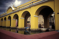 Woman washig clothing in the public laundry washing facility in the Spanish colonial city of Antigua, Guatemala
