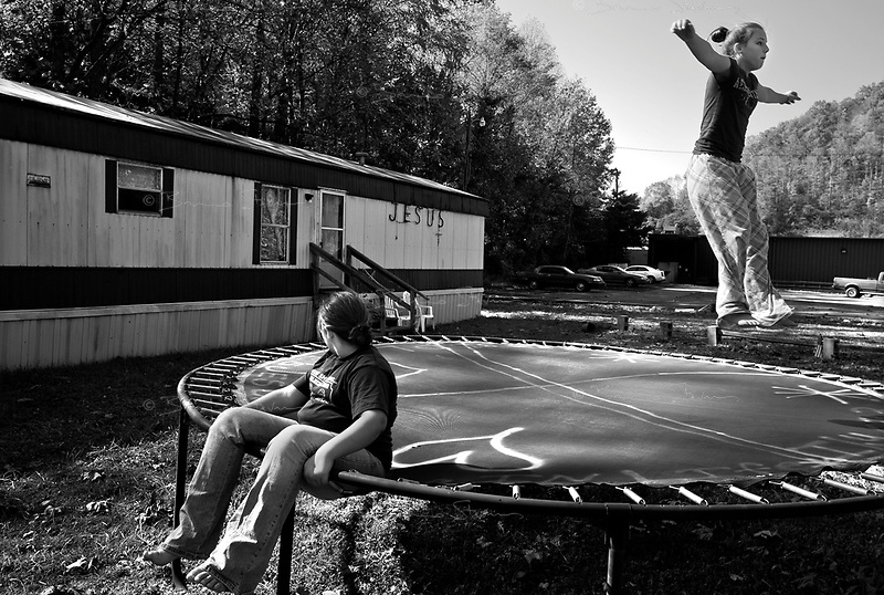 """Gilbert, WV, USA, October 26 2008.Stevie Dawn, 12, flying on the trampoline is the daughter of local pastor Steve Dawson, she wants to become a photographer because """"every picture has a meaning to it""""..Her cousin Kailey, 10, watches her with admiration."""