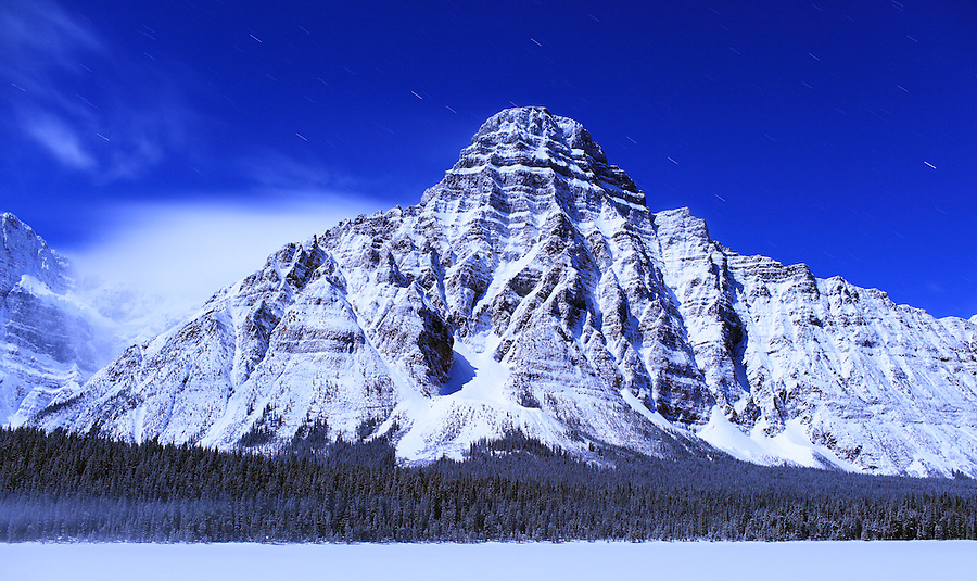 A long exposure leads to streaking stars behind a snow-covered mountainside in Banff National Park, Alberta Canada.