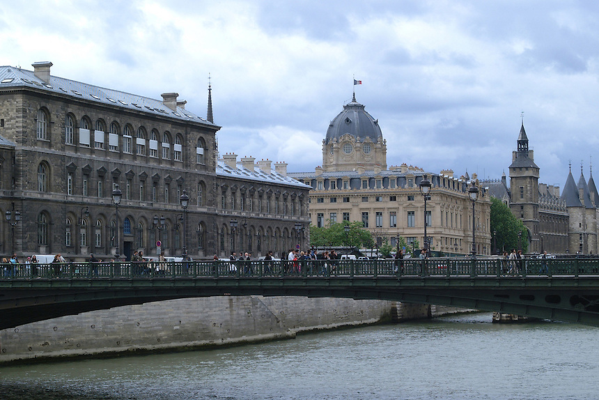 People walking over a bridge over the Seine River, Paris, France, with the Conceirgerie in the background to the right, 2006.