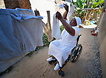 Jennifer Mhlanga suffered a spinal injury in a bus accident, and today uses a wheelchair to get around her home and neighborhood in Harare, Zimbabwe. Here she hangs laundry in the yard of her house. Mhlanga's wheelchair, which was carefully fitted to her individual needs, was provided by the Jairos Jiri Association with support from CBM-US.