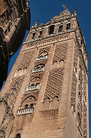 Oblique low angle view of Giralda Minaret, Seville Cathedral, Andalucia, Spain, pictured on December  27, 2006 in the winter morning light. Seville Cathedral is the largest Gothic building in the world. It was converted from the original 12th century Almohad Mosque on this site during the 16th century and the original Moorish entrance court and Giralda Minaret are both integrated in the cathedral. Inside is the tomb of the explorer Christopher Columbus (1451-1506). The Giralda is constructed of cut bricks, originally 82 metres high, now 103 metres high with the 16th century belfry added to the original tower. Picture by Manuel Cohen