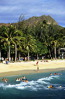 People playing in the surf on the beach at Waikiki with Diamond head in the rear