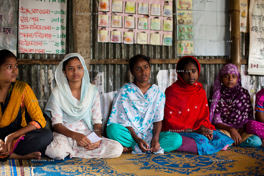 """Mony Mala (16, 3rd from left) speaks during a monthly meeting of a Children's Group in Bhashantek Basti (Slum) in Zon H, Dhaka, Bangladesh on 23rd September 2011. Mony says, """"I'm still a child, not prepared to be a wife. I feel pained that my parents don't see a point in educating me just because I'm a girl. I feel terrible when we are not able to stop a child marriage because the elders do not listen to us."""" The Bhashantek Basti Childrens Group is run by children for children with the facilitation of PLAN Bangladesh and other partner NGOs. Slum children from ages 8 to 17 run the group within their own communities to protect vulnerable children from child related issues such as child marriage. Photo by Suzanne Lee for The Guardian"""