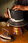 Hat repair shop restores a customer's bowler hat.  The hats are used by the indigenous Aymaran women and is officially called a 'bombin'.  Callejon Tarapaca in La Paz has many milliners making and selling hats, and some who repair them.