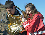 Konstantina Koulouri, a volunteer with the Greek Red Cross, helps a refugee climb off a beach near Molyvos, on the Greek island of Lesbos, on November 2, 2015. The man arrived on a boat full of refugees from Turkey. They were received by local and international volunteers, then proceeded on their way toward western Europe. The boat was provided by Turkish traffickers to whom the refugees paid huge sums to arrive in Greece.