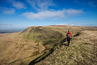 Female hill walker hiking on summit of Picws Du with Fan Brycheiniog in distance, Black Mountain, Brecon Beacons national park, Wales