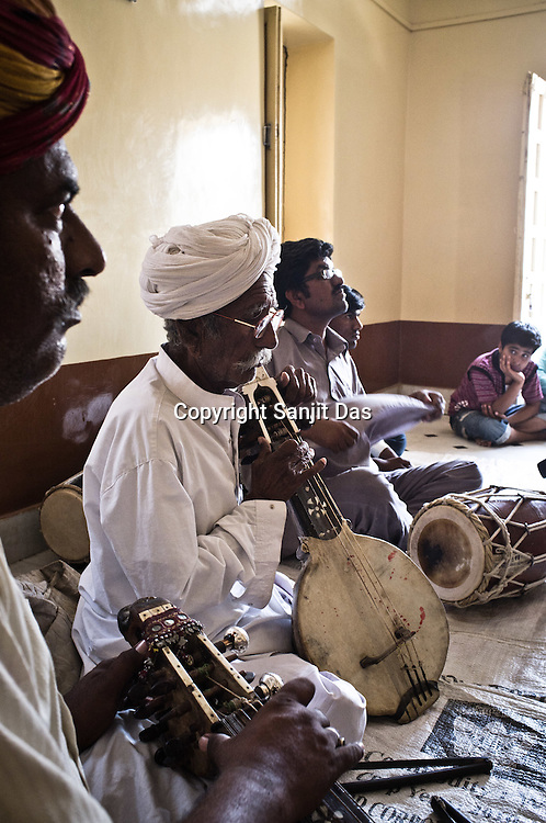 75-year-old Manganiyar artist, Saqar Khan (centre) plays Kamancha (music instrument) while his two sons, Ghewar Khan (45, Left on Kamancha) and Firoze Khan (38, right on Dholak) accompany him during field recordings inside their house in Hamira village of Jaiselmer district in Rajasthan, India. Photo: Sanjit Das/Panos