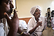 75-year-old Manganiyar artist, Saqar Khan and his son, Ghewar Khan (left) takes a break and smoke biri (local cigarette) inbetween field recordings inside their house in Hamira village of Jaiselmer district in Rajasthan, India. Photo: Sanjit Das/Panos
