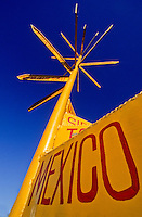 Yellow signpost with directions and mileage to the Worlds major cities. Close up of the Mexico sign.