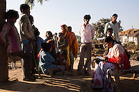 Junior community reporter Sunita (right), 22, interviews villagers in a group in Chitrakoot, Uttar Pradesh, India on 5th December 2012. Sunita and her husband, now sick with TB and unable to work, were estranged from their families because they married against the family's wishes, so Sunita, who had finished her high-school education, supports her husband on the income she makes as a journalist. She makes about 4500 rupees a month. Photo by Suzanne Lee for Marie Claire France.