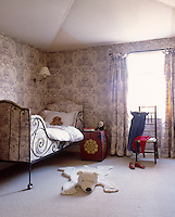 A wrought-iron bed has been upholstered in toile de Jouy to match the walls and curtains in this child's bedroom