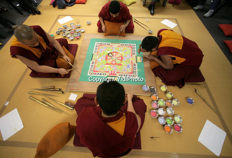 Foto: VidiPhoto..ARNHEM - In Bibliotheek Centrum in Arnhem bouwen Tibetaanse monniken een zogenoemde zandmandala. Een zandmandala symoboliseert een zuivere wereld met vrede en zonder lijden. In een aantal dagen wordt de mandala opgebouwd uit gekleurd zand. Het bezoek aan Arnhem is onderdeel van een Europese tournee om zo geld bij elkaar te brengen voor het noodlijdende klooster en het behoud van Tibetaanse tradities en cultuur.