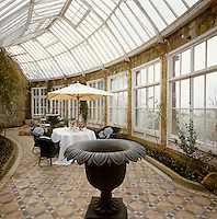 In this curved Georgian conservatory built of warm Bath stone stands a pair of 19th century cast-iron urns