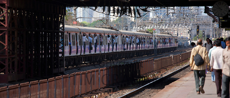 Office workers on crowded commuter train of Western Railway at Mahalaxmi Station on the Mumbai Suburban Railway, India