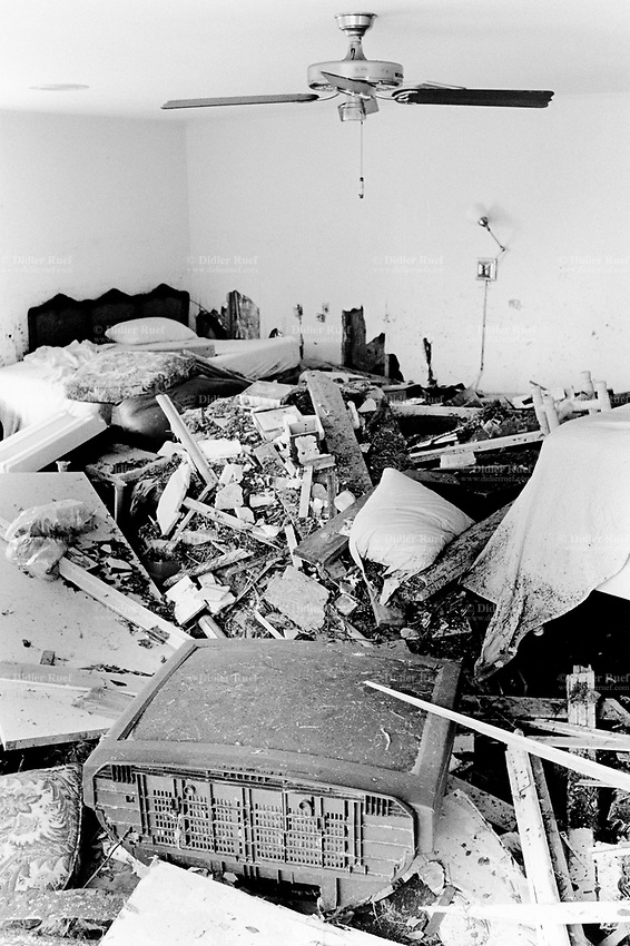 USA. Mississippi. Biloxi. Aftermath of hurricane Katrina. Most houses were  destroyed by the storm, the tidal surge (water wave) and the floods. Interior of a private house with TV set, fan, bed, pillow, table and shelves all destroyed. The house is now empty and all its inhabitants have left away. The people could no longer and ever live again in the houses. The entire area needs to be bulldozed before any new construction can be built. Household waste. Destruction of the urban american way of life.© 2005 Didier Ruef
