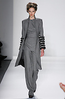 Model walks runway in a black+ivory loro piana cashmere/wool herringbone uptured peak lapel coat, bordered w/pleated tulle/fringe trims+tunic_Trouser, from the Zang Toi Fall 2012 &quot;Glamour At Gstaad&quot; collection, during Mercedes-Benz Fashion Week New York Fall 2012 at Lincoln Center.
