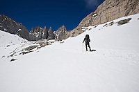 Adult hiker crosses snow on mountaineers route to Mount Whitney, Sierra Nevada Mountains, California