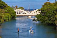 Standup paddleboarders on Anahulu Stream in Haleiwa, North Shore, O'ahu.