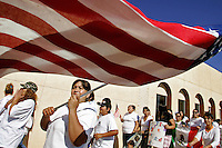 Veronica Serda, left, leads chants as Victoria Flores, center, and other immigrant rights supporters march down Main St. in Clovis, N.M. on Tuesday morning.