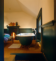 A free-standing roll-top bath stands next to the window in this green bathroom with an open fire