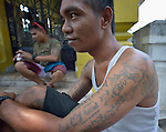 """Tattoos on the arm of a young man in the Manila North Cemetery. Hundreds of poor families live here, dwelling in and between the tombs and mausoleums of the city's wealthy. They are often discriminated against, and many of their children don't go to school because they're too hungry to study and they're often called """"vampires"""" by their classmates. With support from United Methodist Women, KKFI provides classroom education and meals to kids from the cemetery at a nearby United Methodist Church."""