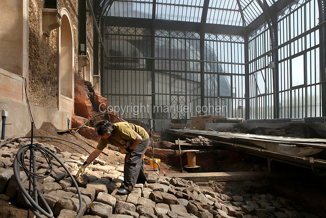 New Caledonia Glasshouse (formerly The Mexican Hothouse), 1830s, Charles Rohault de Fleury, Jardin des Plantes, Museum National d'Histoire Naturelle, Paris, France. Low angle view of a worker putting old paving stones into position. They will be covered with soil to form a drainage system. The New Caledonia Glasshouse, or Hothouse, was the first French glass and iron building. Through the windows the Tropical Rainforest Glasshouse (formerly Le Jardin d'Hiver or Winter Gardens), 1936, René Berger, is visible.