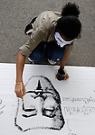 BANGKOK, July 14: A protestor paints a Guy Fawkes mask on a banner when anti-government protestors supporting the white-mask movement against corruption in the Yingluck Shinawatra government gathered at Lumpini Park on the second anniversary of the Yingluck administration to protest the blatant corruption in government policy and practice. July 14, 2013, Bangkok, Thailand