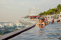 Tourists in the  Sky Park swimming pool on the roof of the Marina Bay Sands resort hotel which has spectacular views over the Singapore skyline.