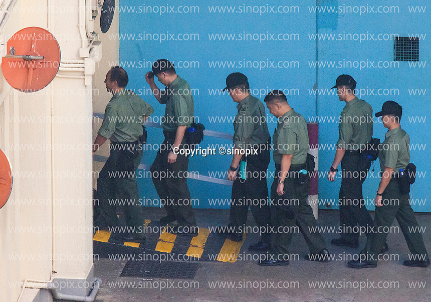 Prison guards enter a doorway off a courtyard at the Lai Chi Kok Reception Centre shortly before British ex-banker Rurik Jutting boarded a high security prison van to bring him to his trial at the High Court of Hong Kong for the alleged killing of two Indonesian women in October 2014, Hong Kong, China, 01 November 2016.