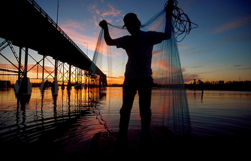 Scenic silhouette of a fisherman near a bridge holding a bait net at sunrise. Louisiana.