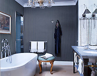 In a master bathroom, the bathtub fittings are by Lefroy Brooks, and the 1750 Italian stool is a family heirloom; the walls are lined with a wallcovering by Ralph Lauren Home, and the 1930s chandelier is by Venini. A sleek nickel-and-glass doors lead to a steam shower and bath.