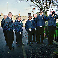Flag bearers stand in a group at the 2010 Remembrance Sunday service for the North Belfast battalion of the Ulster Defence Association (UDA) at Tigers Bay estate. In the past this occasion would have been showcased with a full colour parade with UDA members wearing military uniforms and firing guns as a mark of respect.