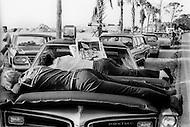 Cape Kennedy, FL - July 16, 1969, 5am.<br /> People sleeping on the hoods of their car waiting to watch the launch of Apollo XI at Kennedy Space Center. As weather conditions must be perfect for a space launch, no exact time was given to the public for takeoff. Crowds of spectators arrived early to camp out, leading to a party like event. <br /> Cape Kennedy, Floride, 16 juillet 1969. 5 heures du matin.<br /> Le temps exact n&rsquo;a pas &eacute;t&eacute; donn&eacute; pour le lancement de la fus&eacute;e, les plus astucieux ont pu faire fonctionner leur TV sur la batterie de leurs v&eacute;hicules. Toutes les chaines couvriront en directe le lancement d&rsquo;Apollo XI et un demi milliard de t&eacute;l&eacute;spectateurs seront devant leurs &eacute;crans de t&eacute;l&eacute;visions.